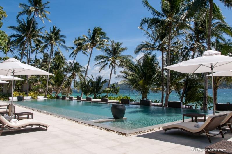 椰子の木と沖合に浮かぶ島々の景観を楽しめるプール